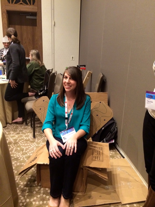 Kristie sitting in the chair we made from cardboard, brads, and nails in 20 minutes in the maker session.